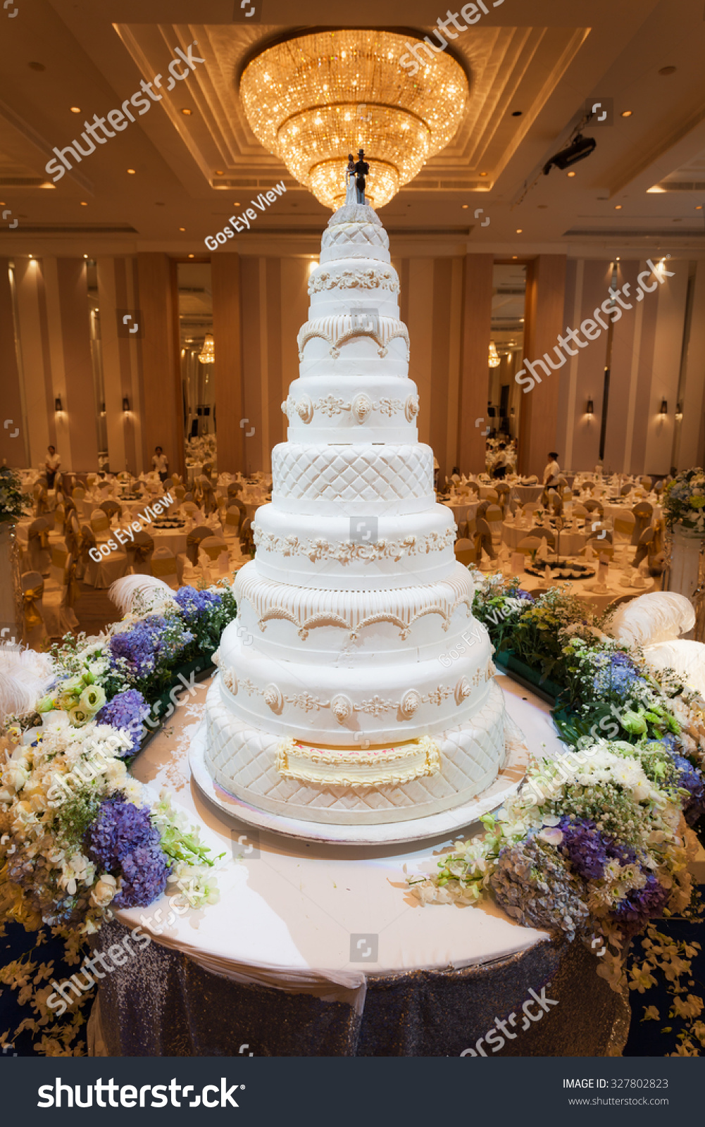 Flowers decorations around wedding cake chandelier stock photo flowers and decorations around wedding cake with chandelier on ceiling arubaitofo Image collections