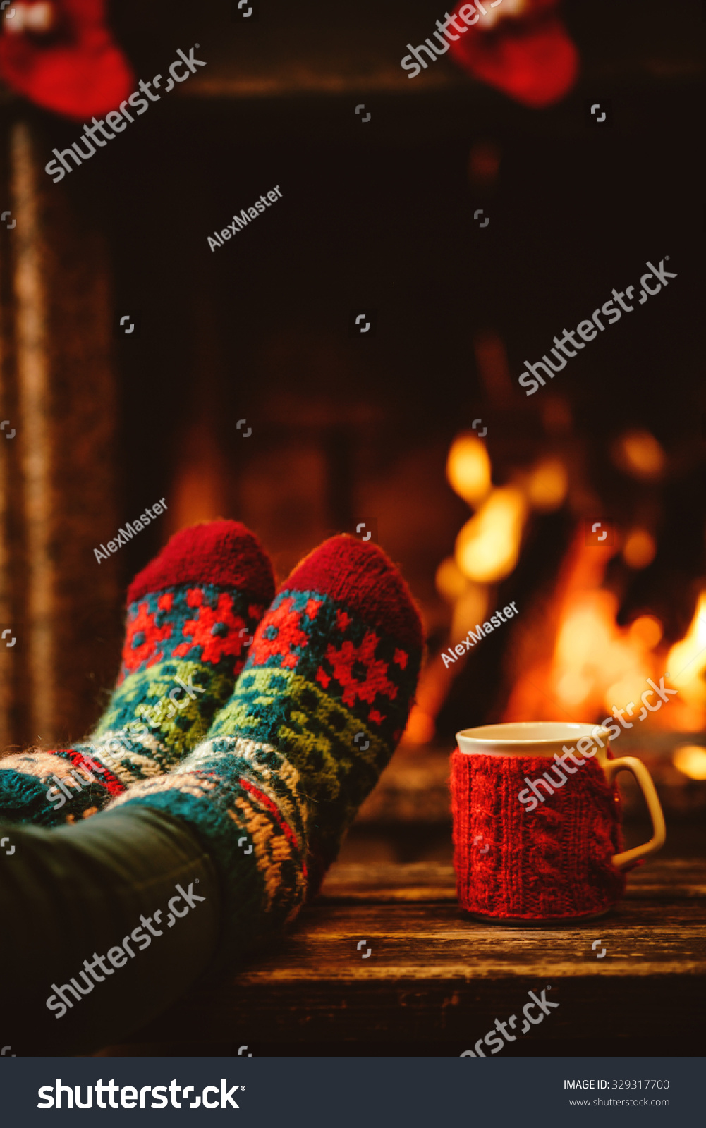 Feet in woollen socks by the Christmas fireplace Woman relaxes by warm fire with a cup of hot drink and warming up her feet in woollen socks Close up on feet Winter and Christmas holidays concept