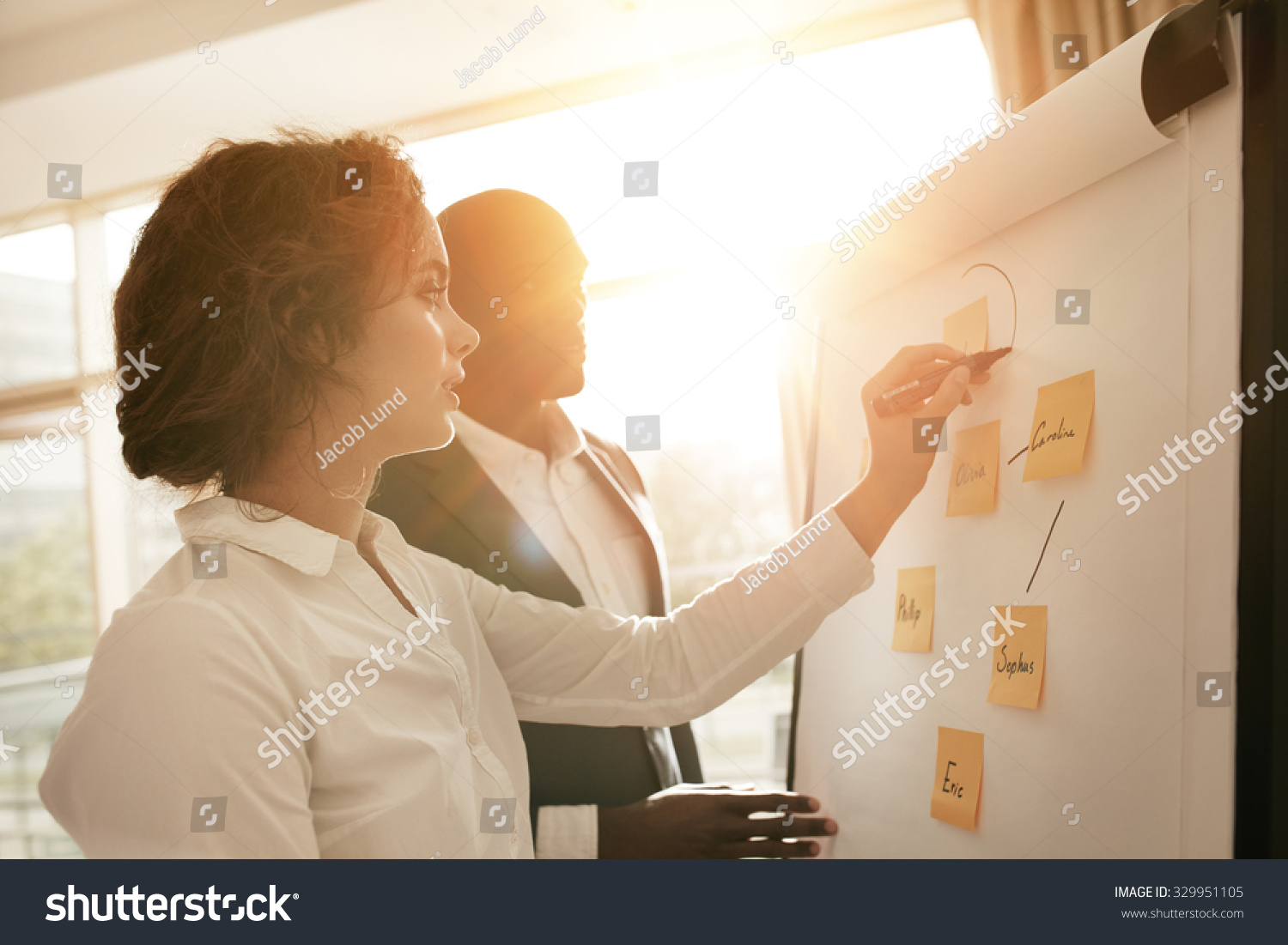 Two Young Associates Working Together Drawing Stock Photo ...