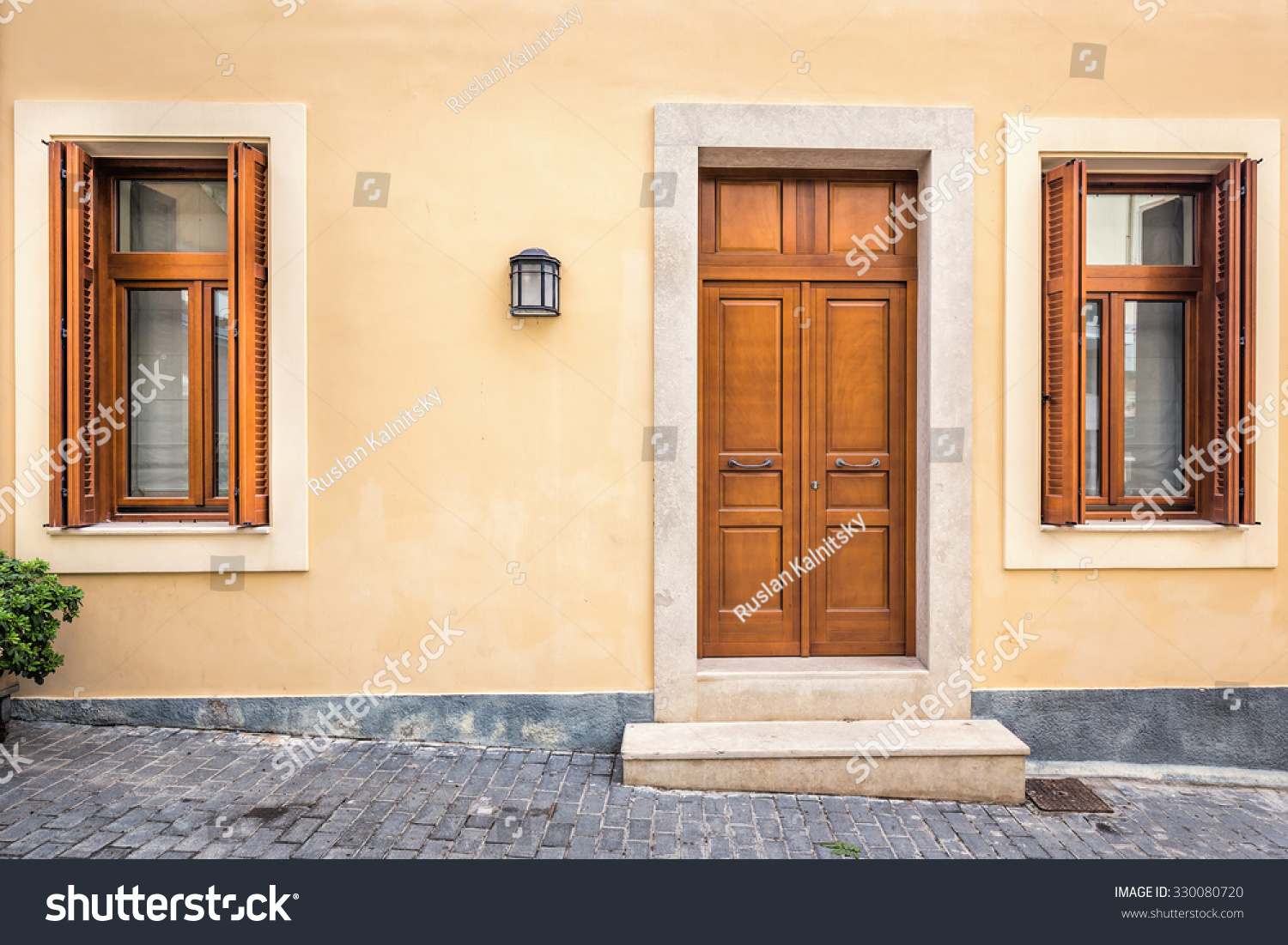 Wood Door And Windows With Wooden Shutters On Peach Colored Wall At  Santorini, Greece.