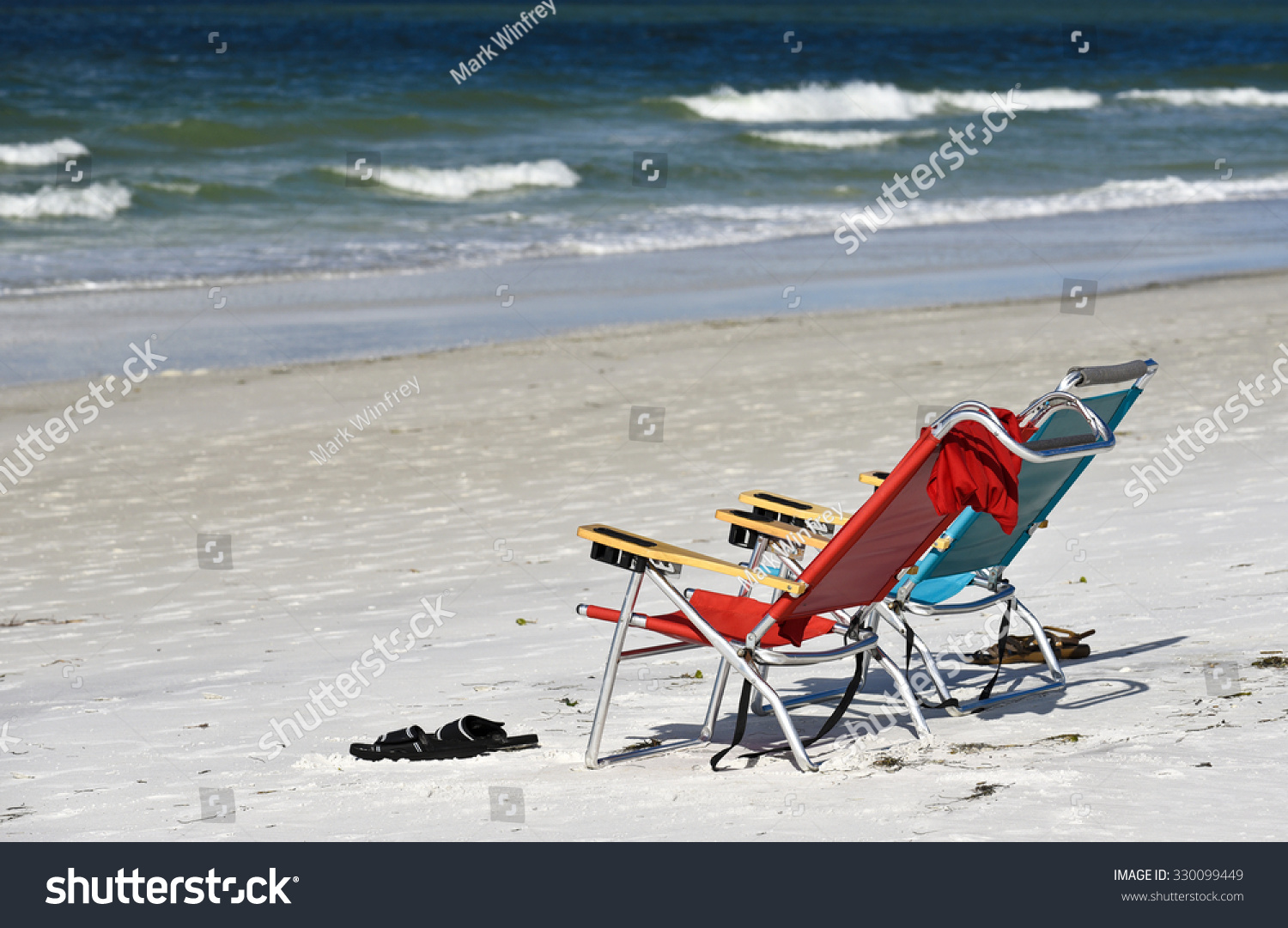 Two Empty Beach Chairs on the Beach facing the Ocean
