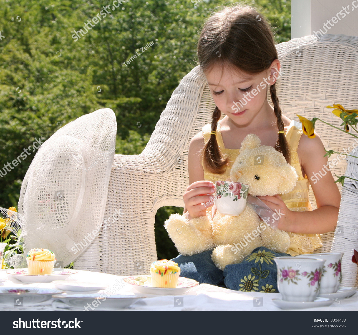 Little Girl In Wicker Chair Having Tea Party With Teddy