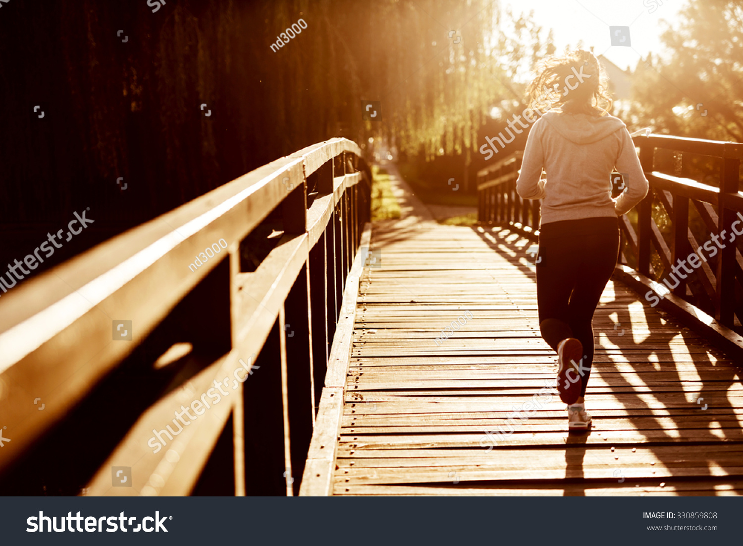 Beautiful female jogger running during sunset across bridge
