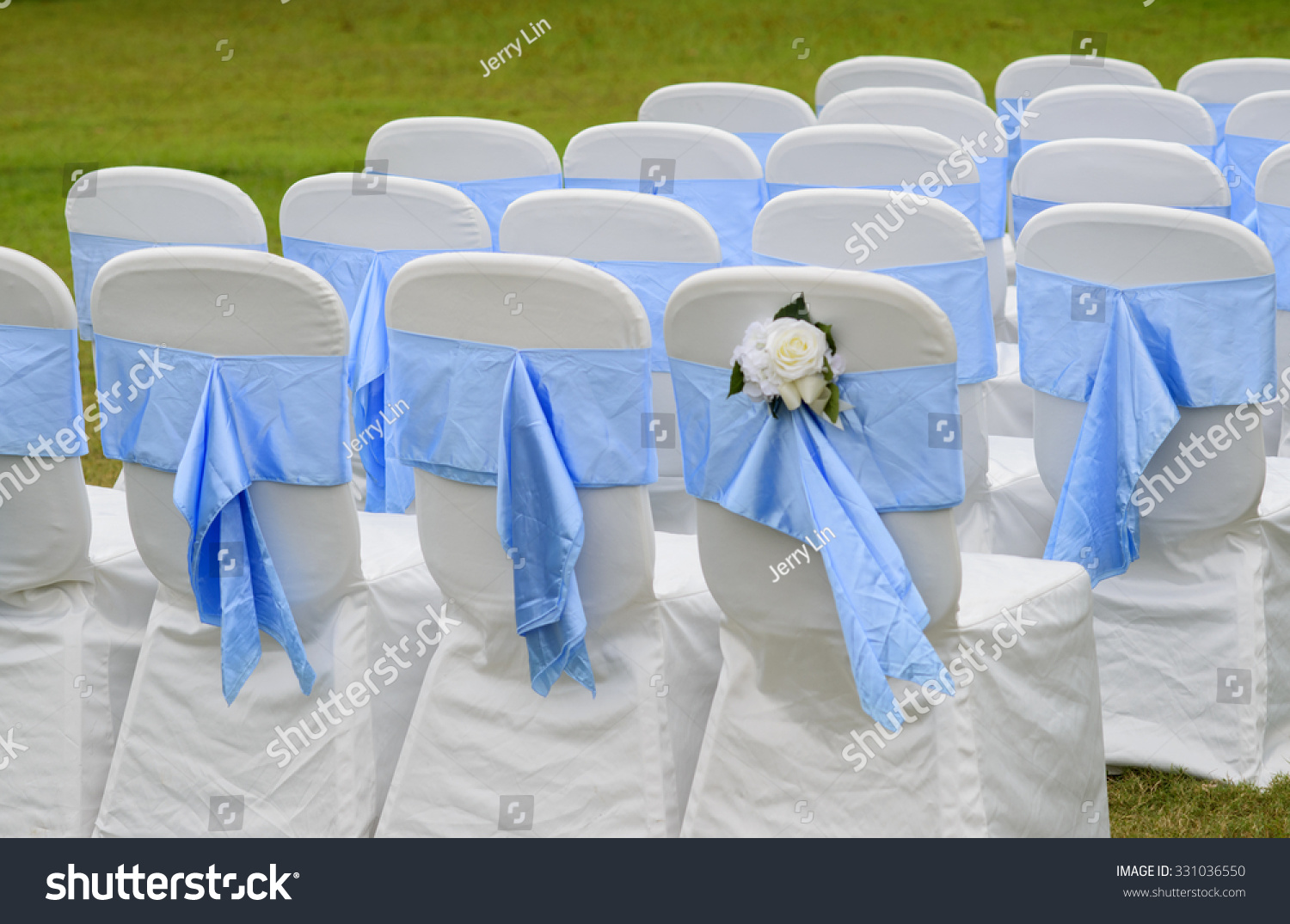 Beautiful White Wedding Chairs Decorated With Blue Bows
