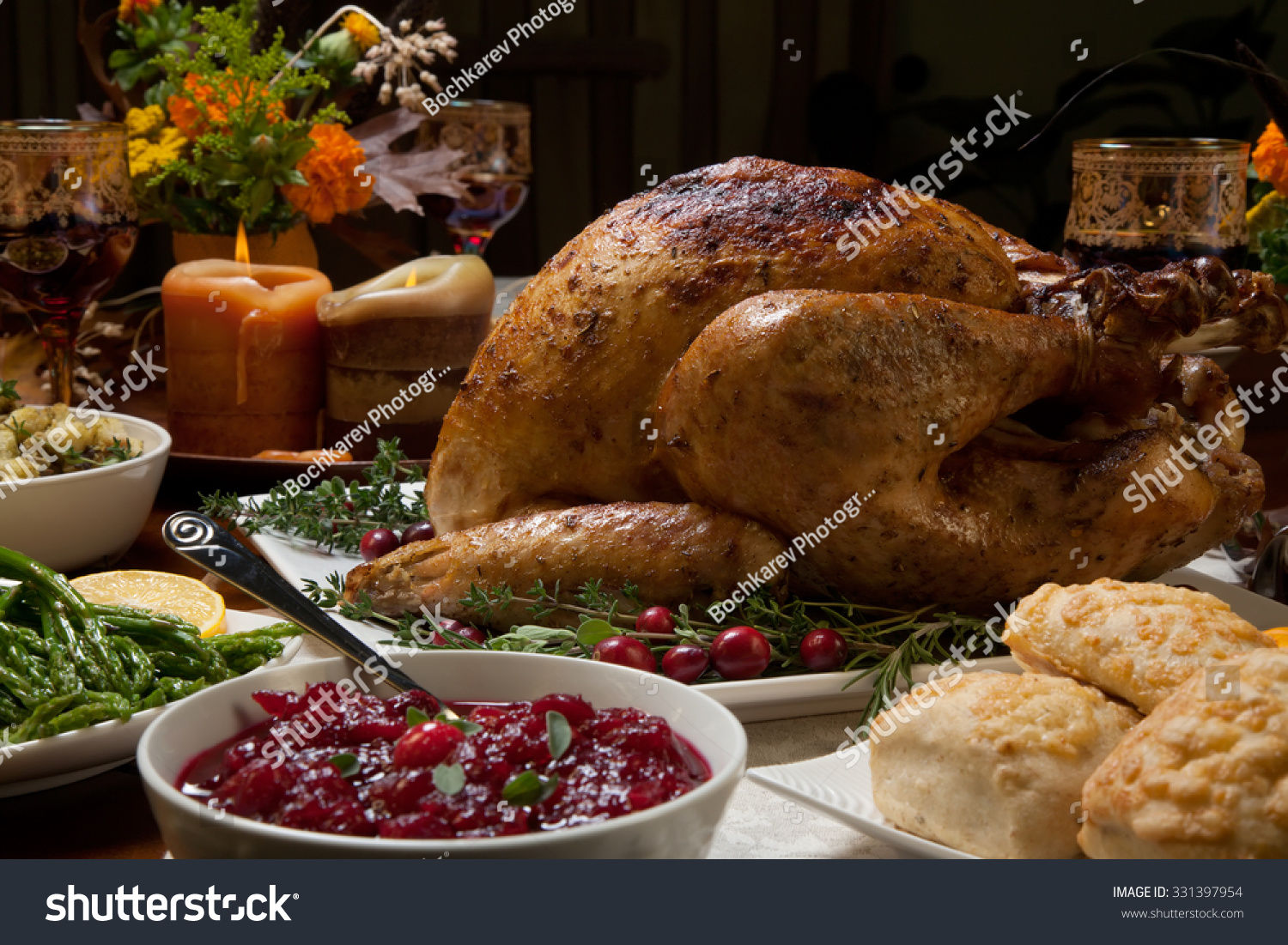 Roasted turkey garnished with cranberries on a rustic style table ...