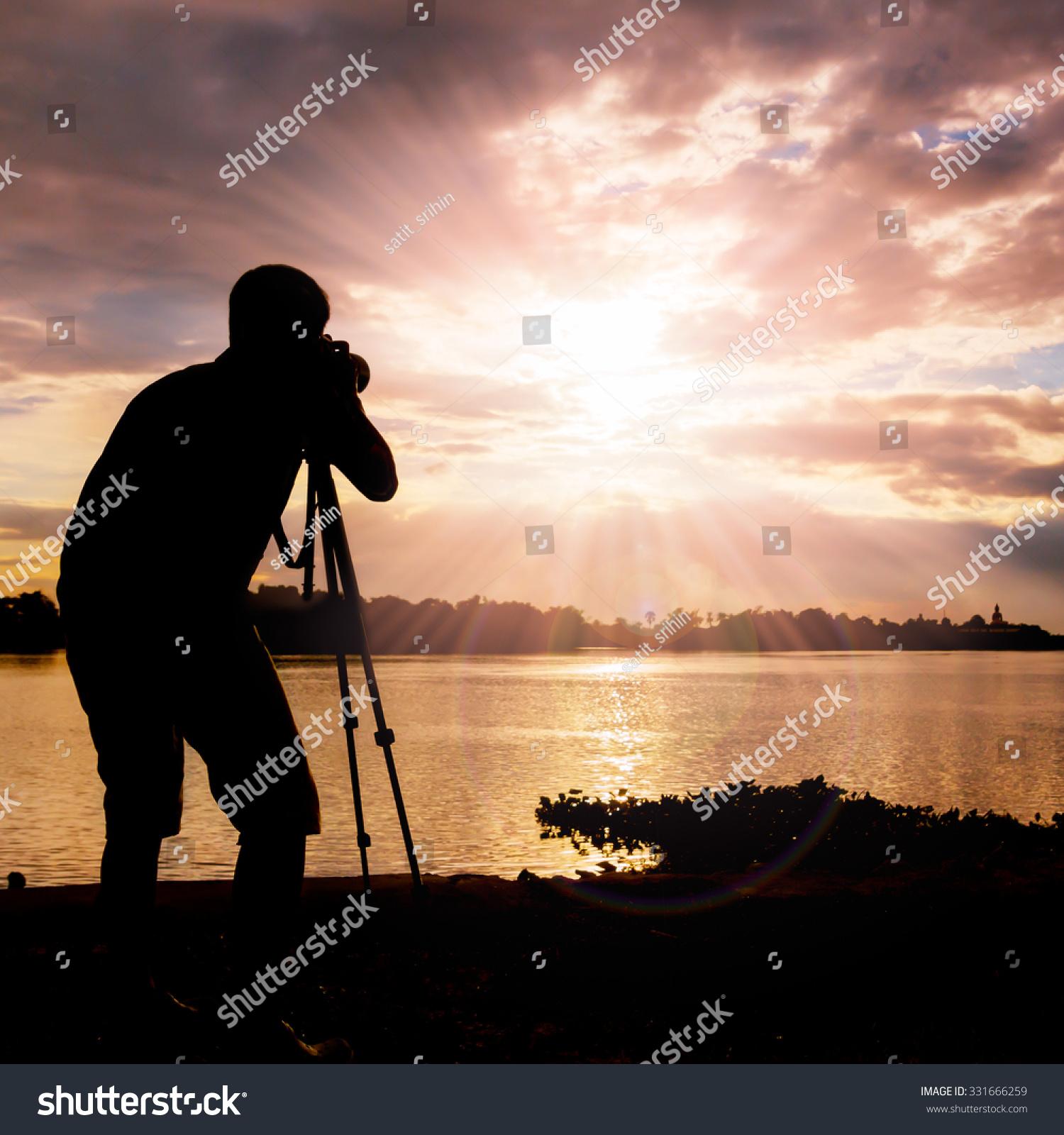 Silhouette grapher Taking Sunset Sunray Stock