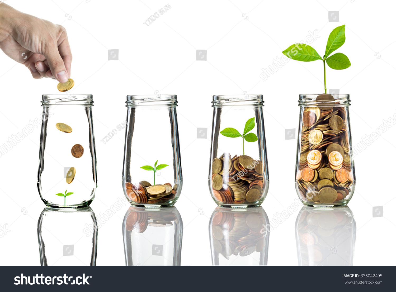Hand putting gold coins into clear bottle on white background,Business investment growth concept #335042495