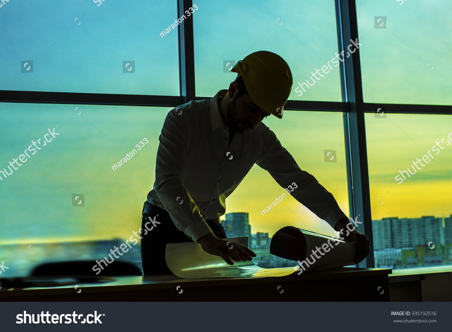 Royalty free silhouette builder engineer wear 335192516 stock silhouette builder engineer wear security helmet look at blueprint paper construction drawing plan on background of malvernweather Image collections