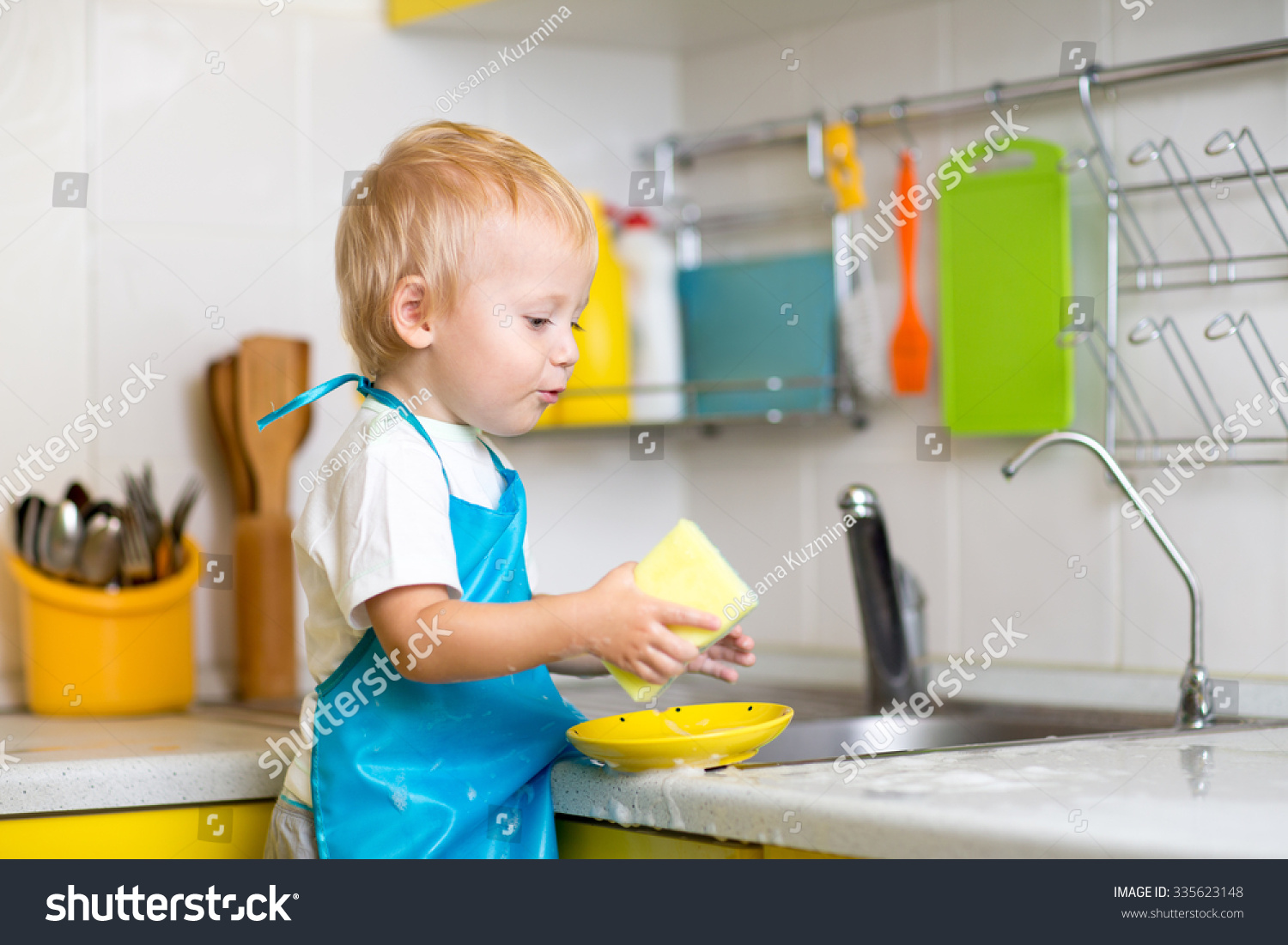 Child Boy Cleaning Kitchen After Dinner Stock