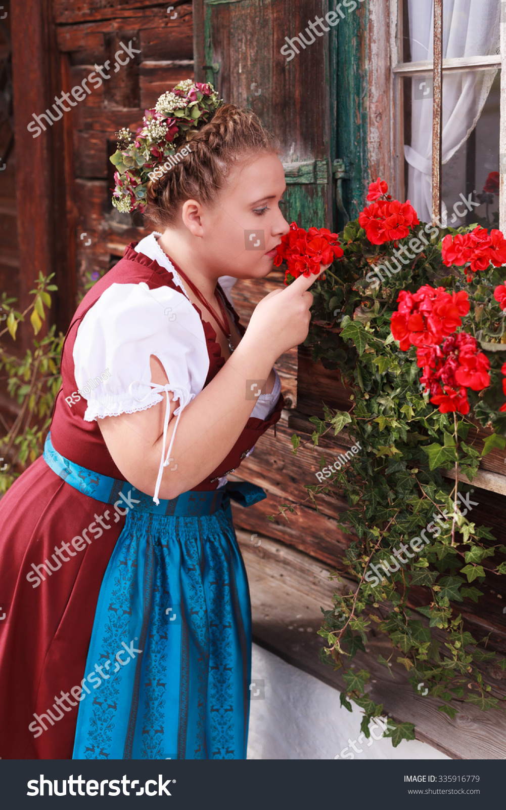 Young, Bavarian, chubby girl in red dirndl smelling a geranium in a flower  box