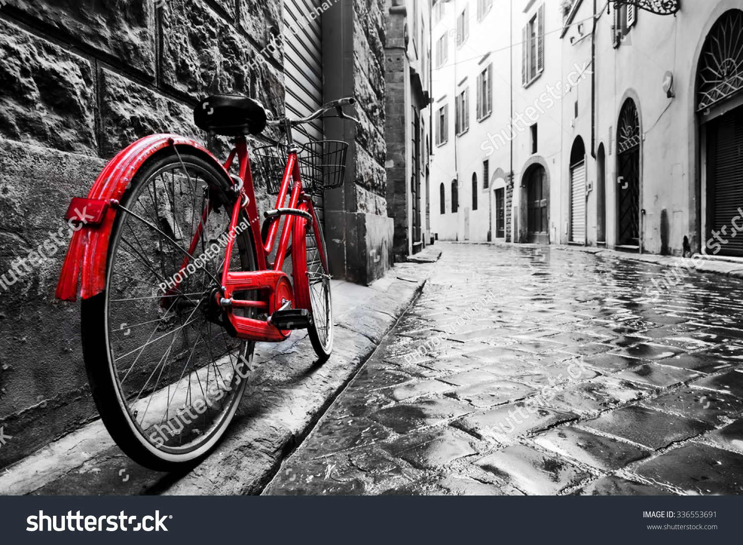 Retro vintage red bike on cobblestone street in the old town. Color in black and white. Old charming bicycle concept. #336553691