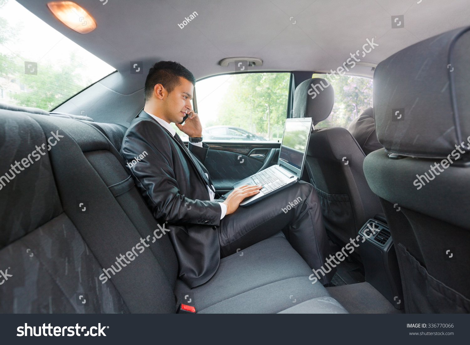 Businessman using laptop and mobile phone while commuting to work by taxi