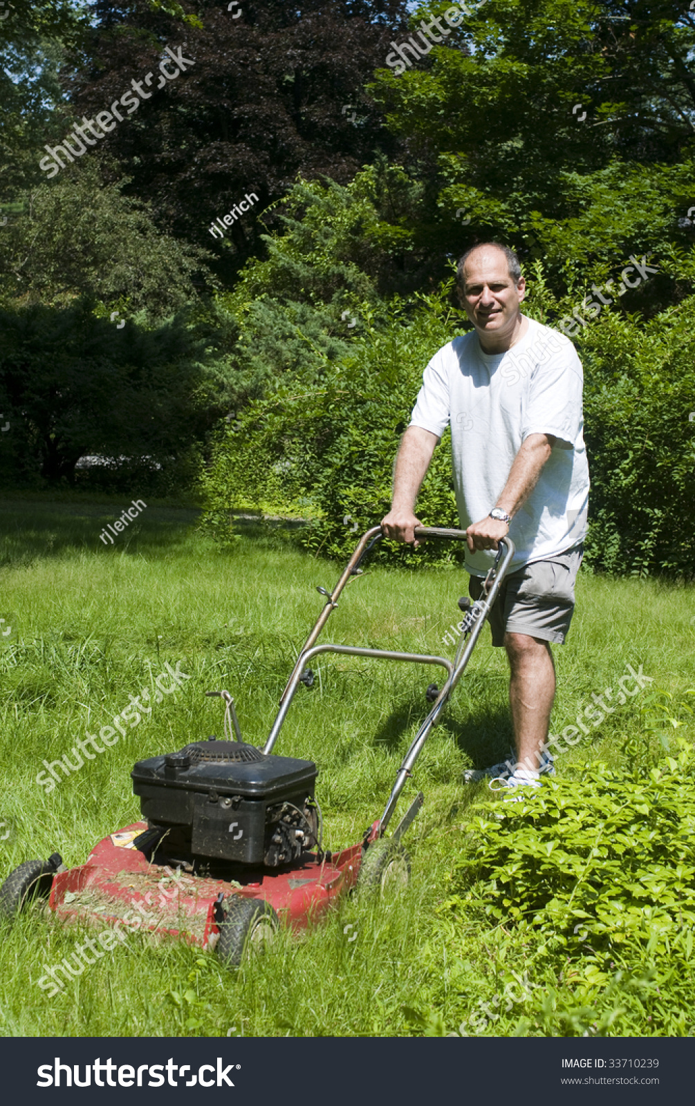 handsome middle age man cutting overgrown grass with old fashioned lawn mower at suburban house. Black Bedroom Furniture Sets. Home Design Ideas