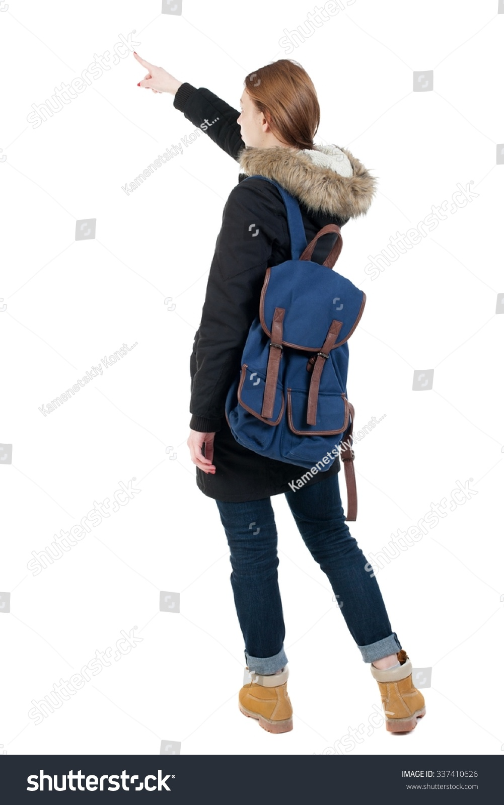 60c2fd8c69 Back view of pointing young women in parka with backpack. Young girl  gesture. Rear view people collection. backside view of person.