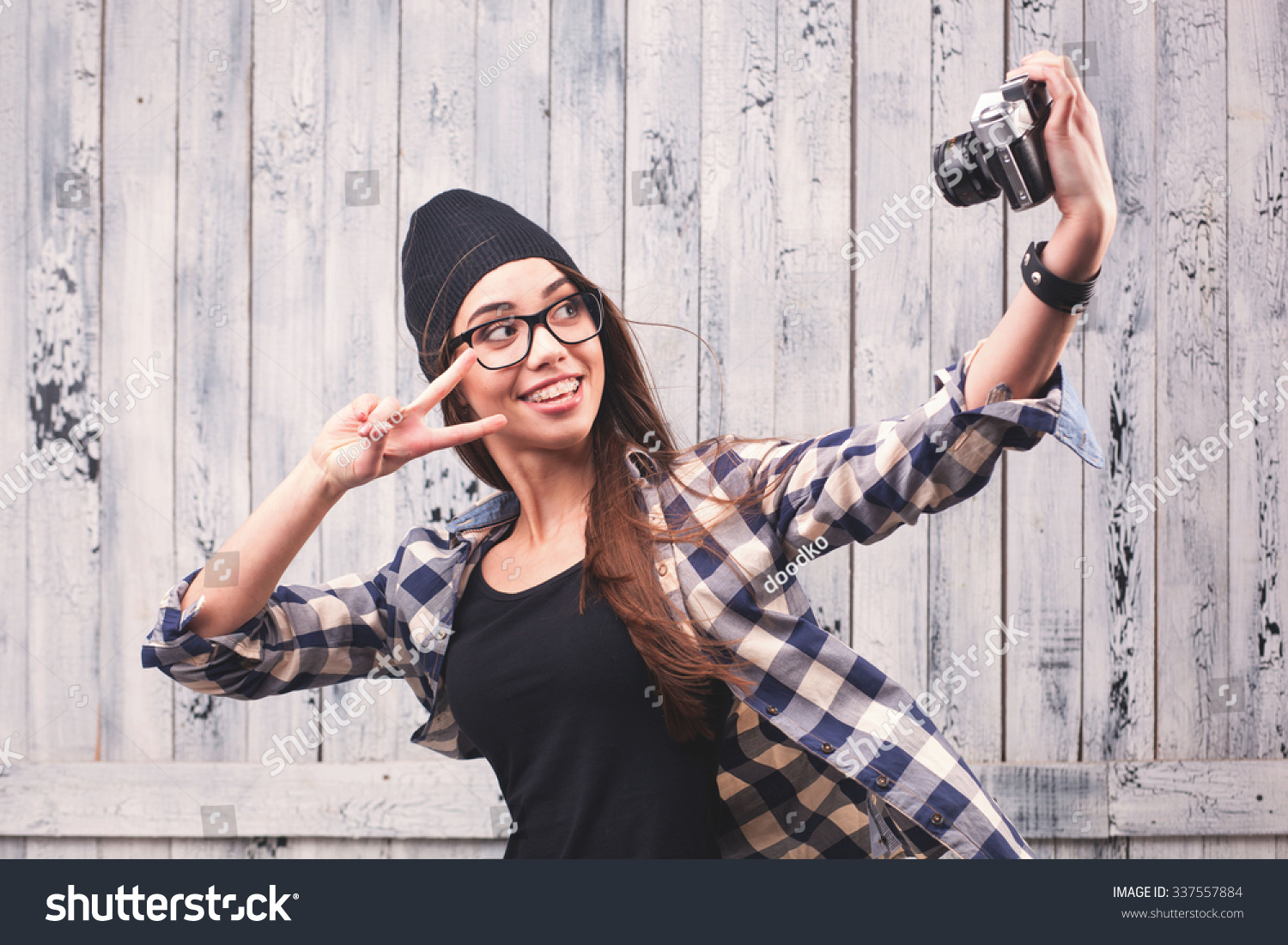7f2e6d9c62d Hipster girl in glasses and black beanie making selfieshot with vintage  camera on the wooden background