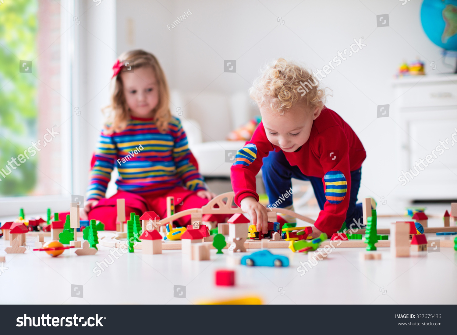 Children playing with wooden train Toddler kid and baby play with blocks trains and cars Educational toys for preschool and kindergarten child Boy and girl build toy railroad at home or daycare