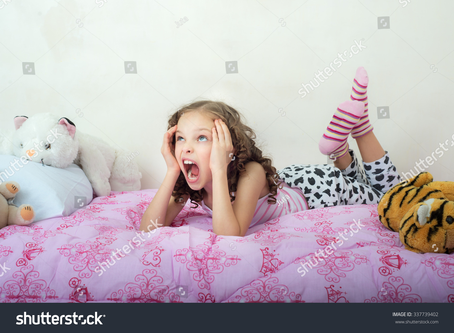 little girl lying Screaming little girl lying on her bed. Facial expression, Emotions.