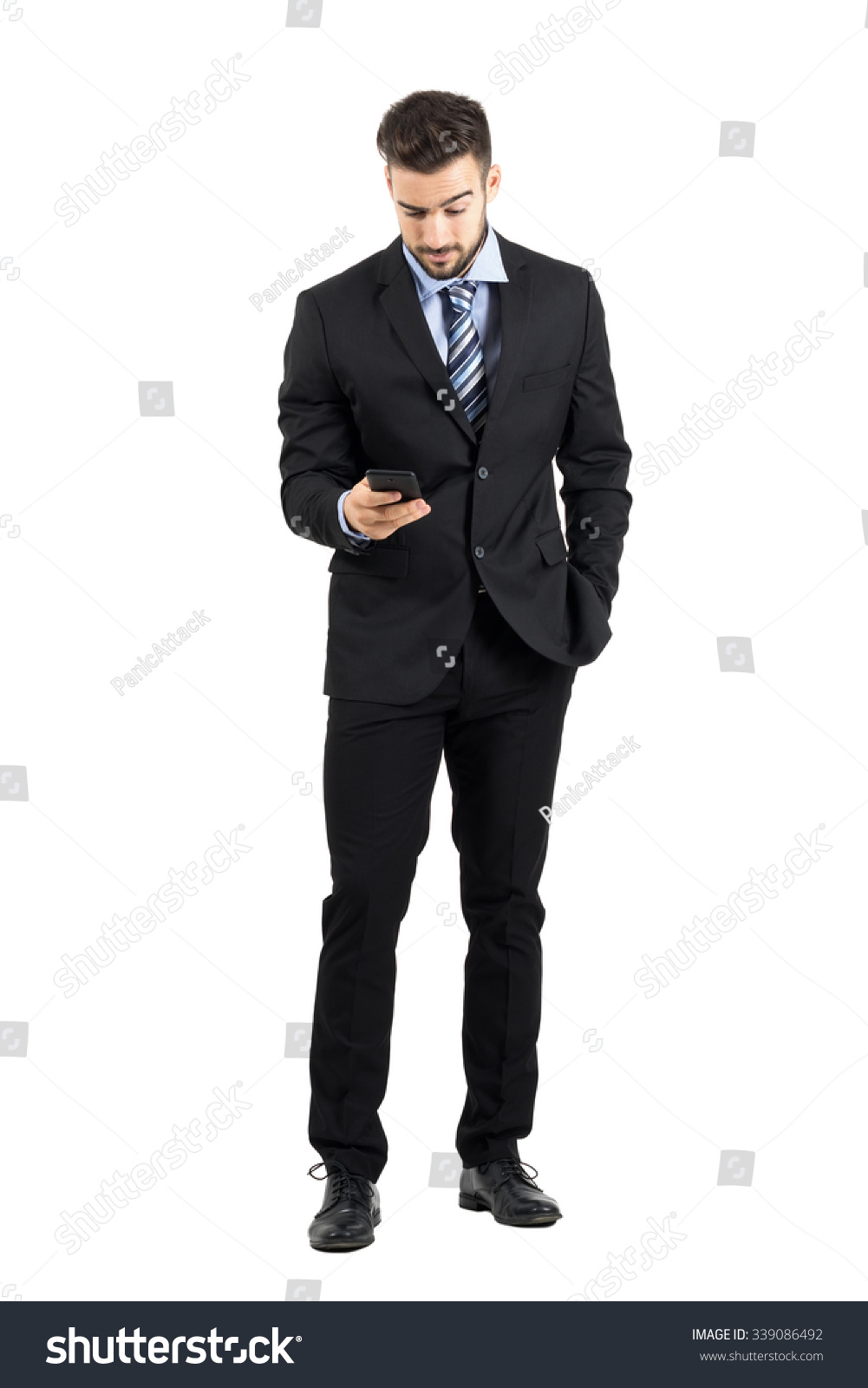 4e6be6a4c2 Young business man in suit reading message on his cellphone. Full body  length portrait isolated