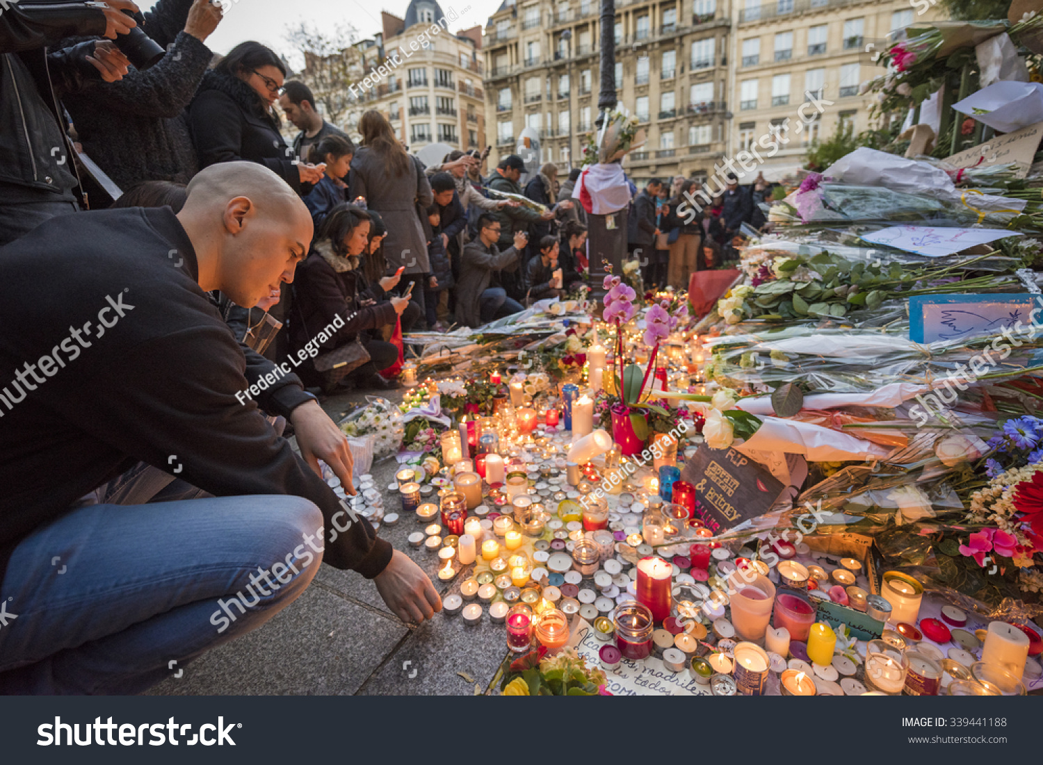 PARIS FRANCE NOVEMBER 15 2015 A man lights a candle in front of the theater Le Bataclan in tribute to victims of the Nov 13 2015 terrorist attack in Paris at the Bataclan