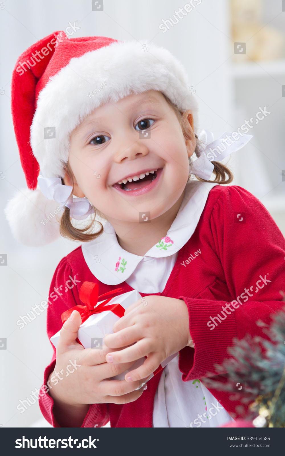 Portrait of a cute little girl in santa hat with Christmas gifts ...