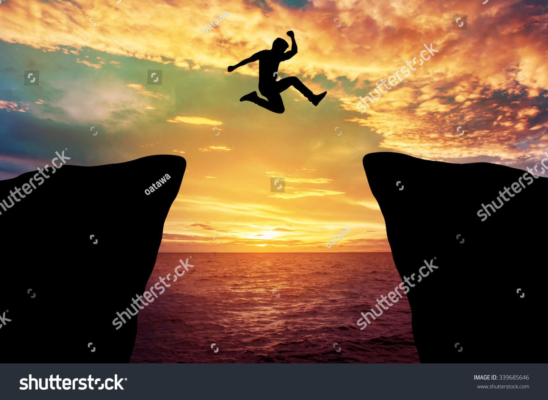 Man jump through the gap between hill stock photo for Jump the gap