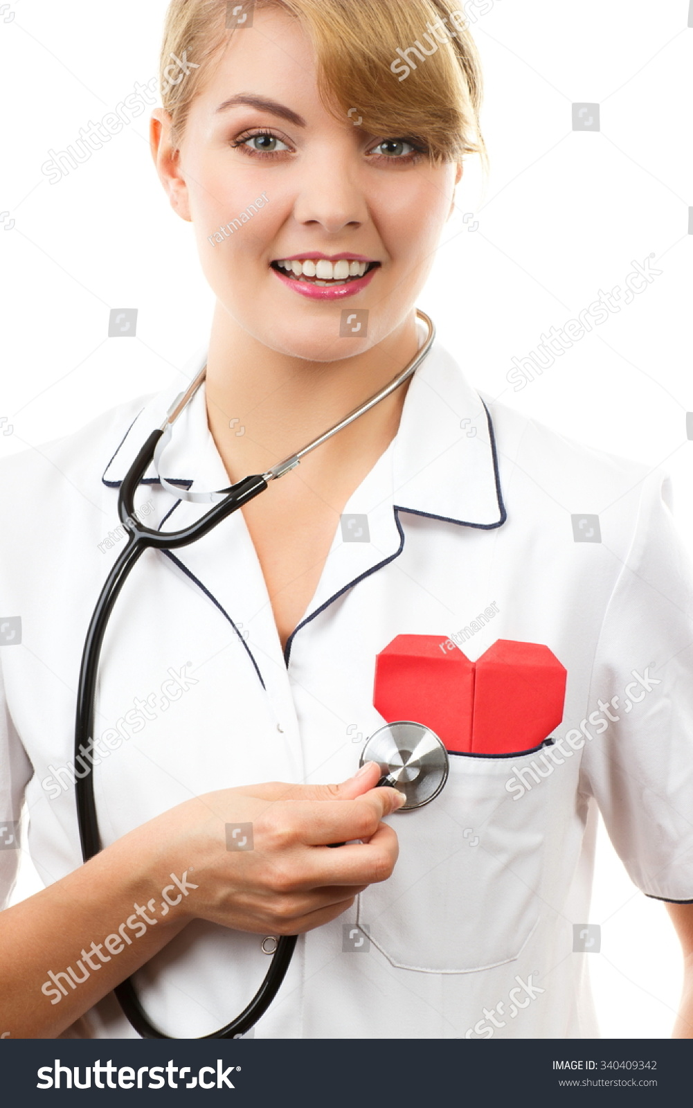 White apron health - Smiling Woman Doctor Cardiologist In White Apron With Stethoscope Examining Red Heart Healthcare And Medicine