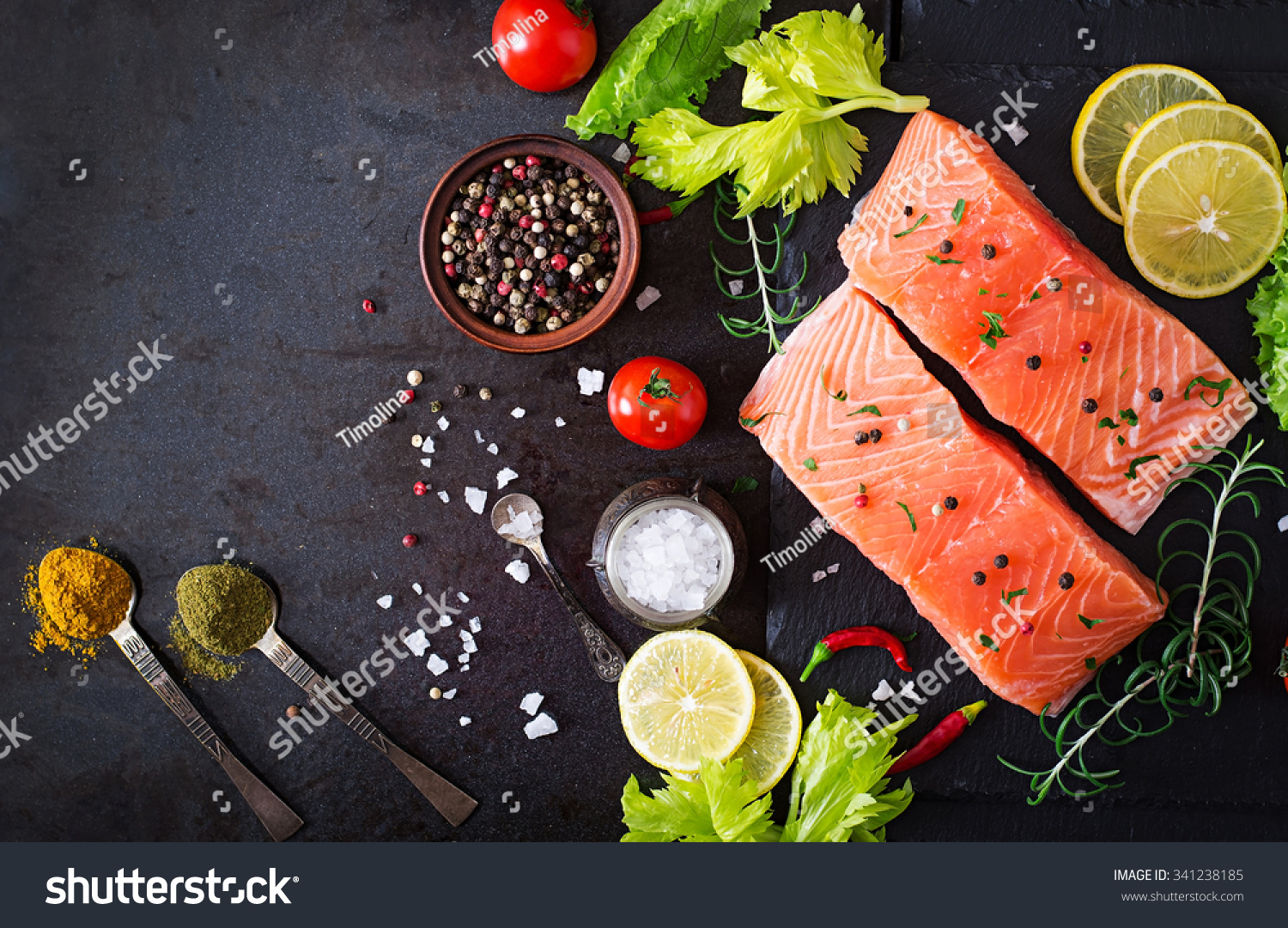 Raw salmon fillet and ingredients for cooking on a dark background in a rustic style Top view