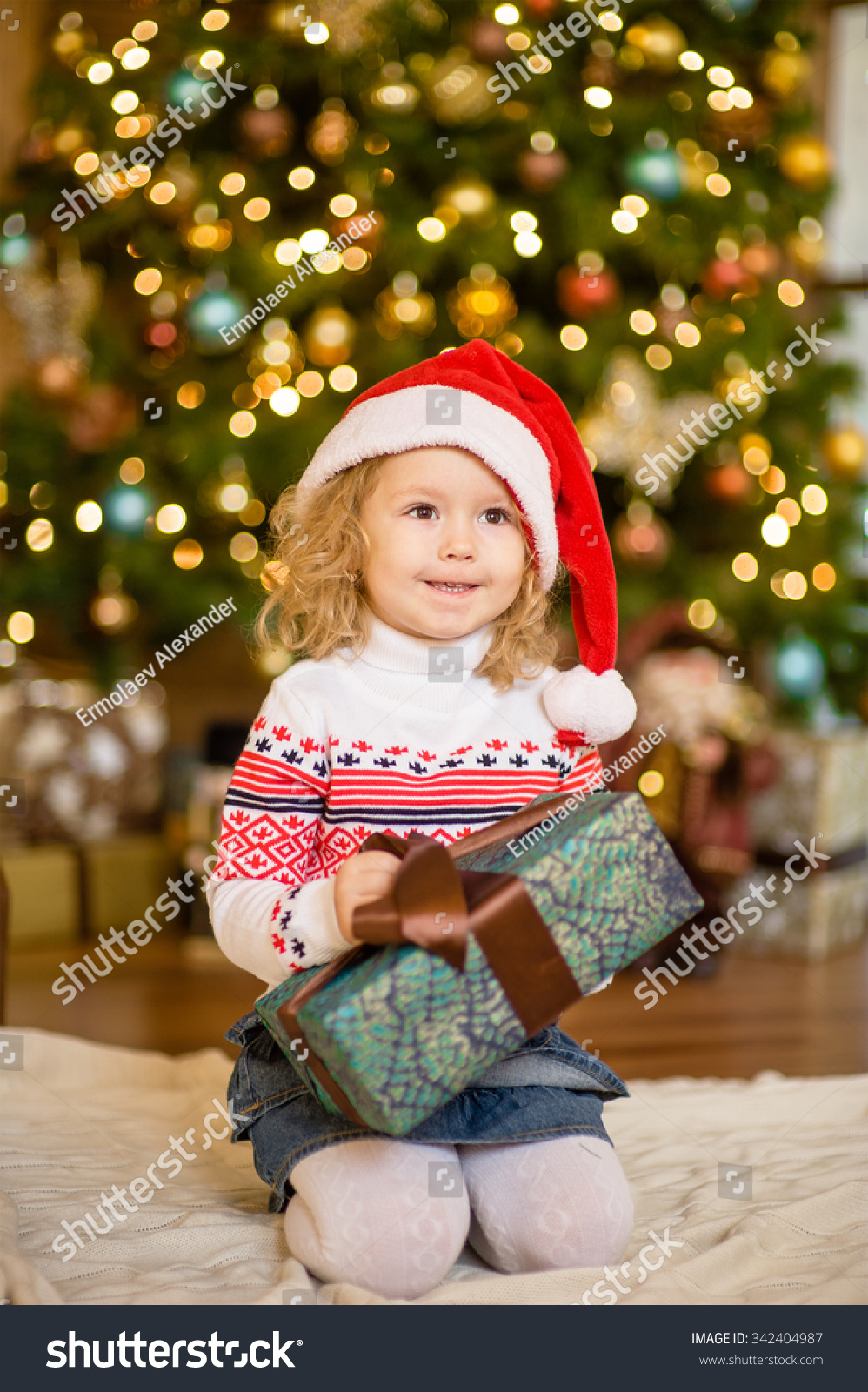 Little girl in red santa hat holding christmas gift box | EZ Canvas