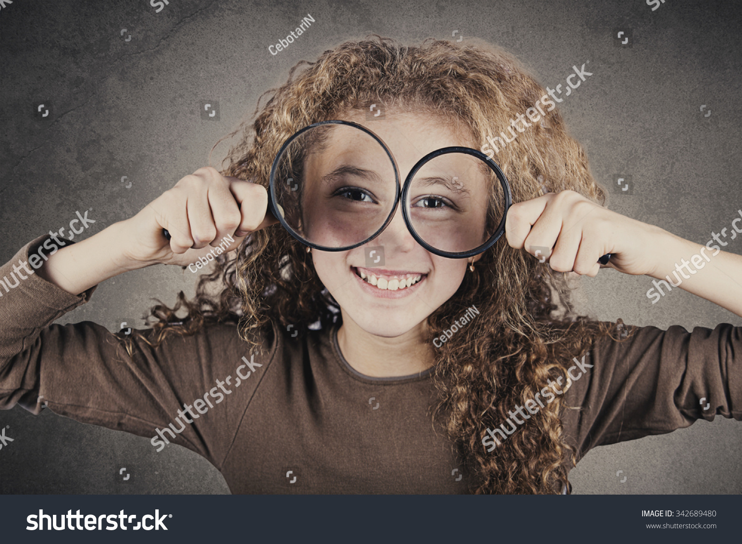 fca8efa606e4 Funny portrait of cute little girl looking through magnifying glass.Curious  Smiling little girl looking