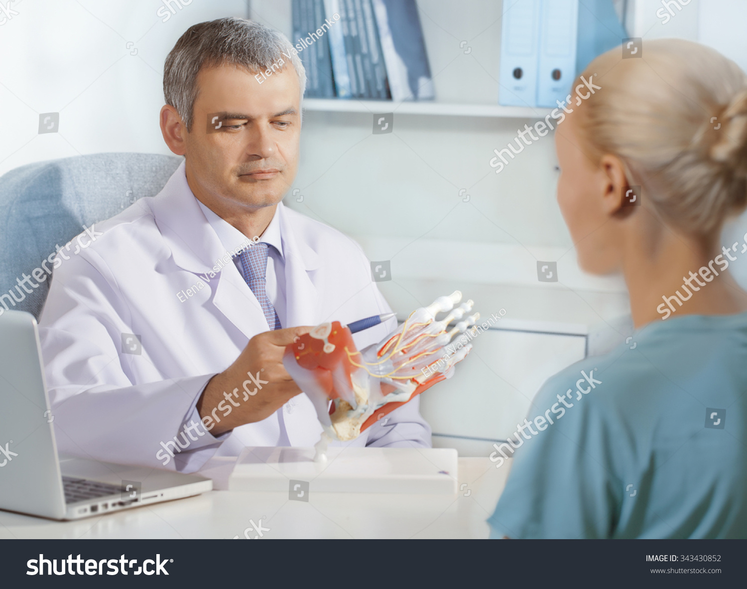 Orthopedic Doctor In His Office With The Model Of Feet And Patient