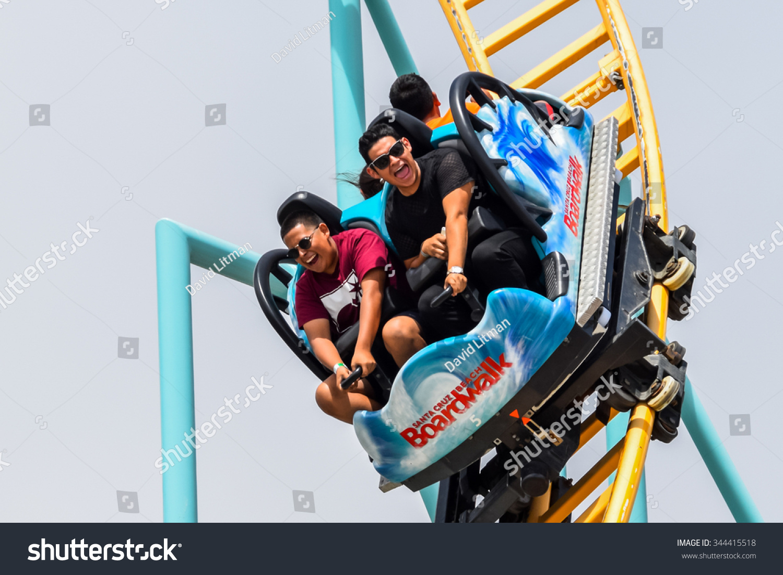 Santa Cruz, California, USA - July 5. 2015: A group of people enjoy a fast roller coaster ride  (Undertow) at the Santa Cruz Beach Boardwalk amusement park during the Fourth of July holiday weekend.