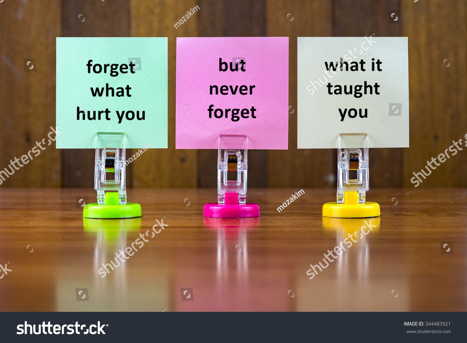 Word Quotes Of FORGET WHAT HURT YOU BUT NEVER FORGET WHAT IT TAUGHT YOU On  Colorful Sticky Papers Against Wooden Textured Background. Stock Photo