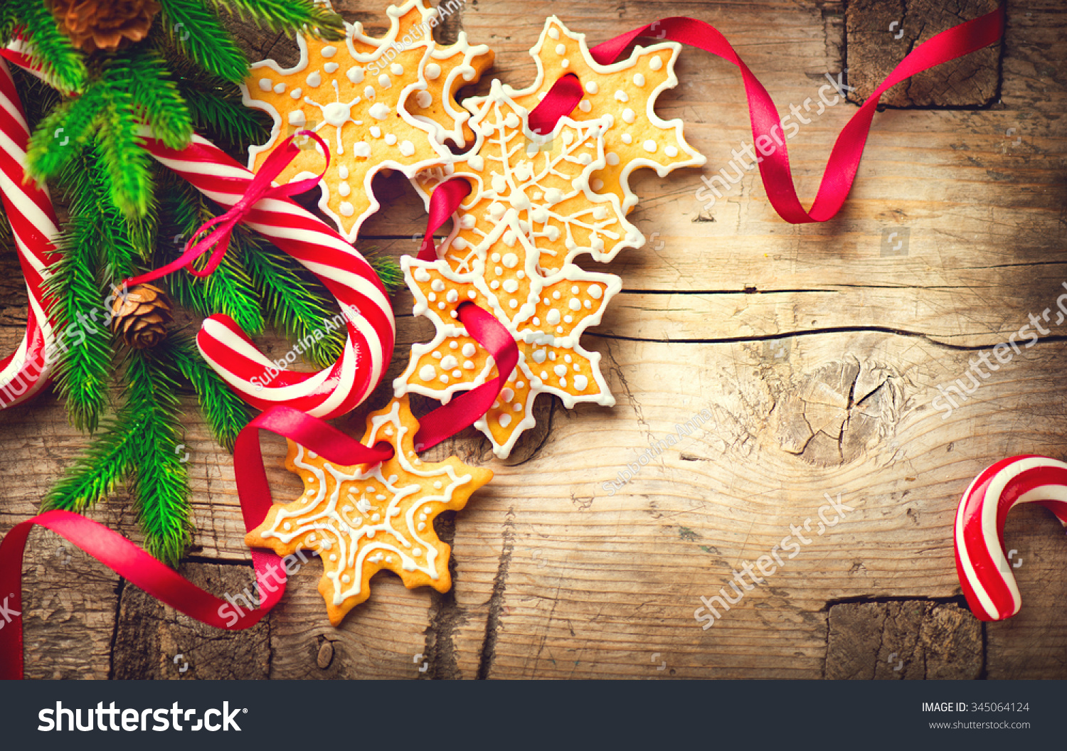 christmas holiday background with gingerbread cookies candy cane and evergreens border over wooden table