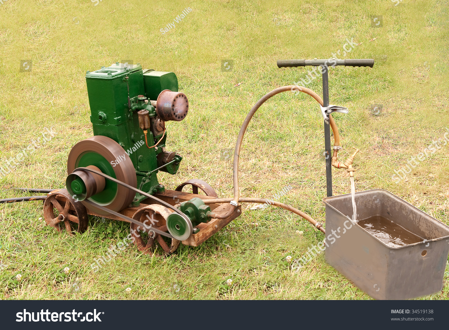 Ancient Belt Driven Motor Pump Filling A Tank With Water