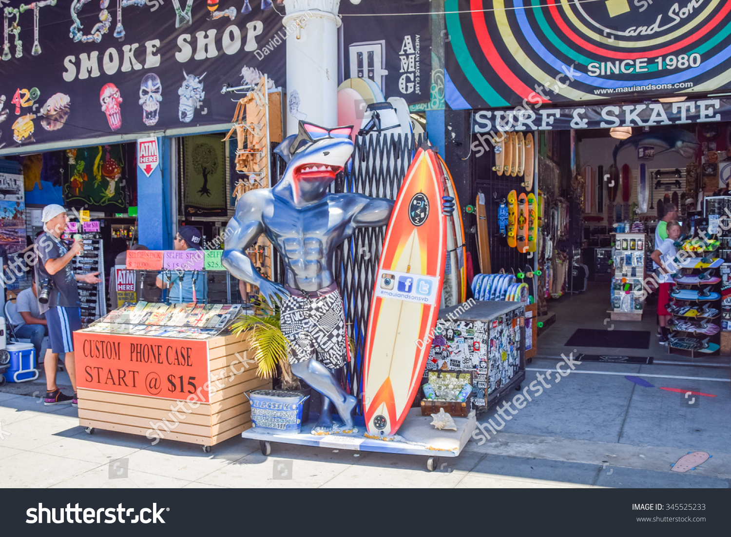 Venice, California, USA - July 12, 2015: Colorful storefronts, including a body building  land shark with surfboard, a smoke shop and a surf shop, line the boardwalk in Venice Beach, California, USA.