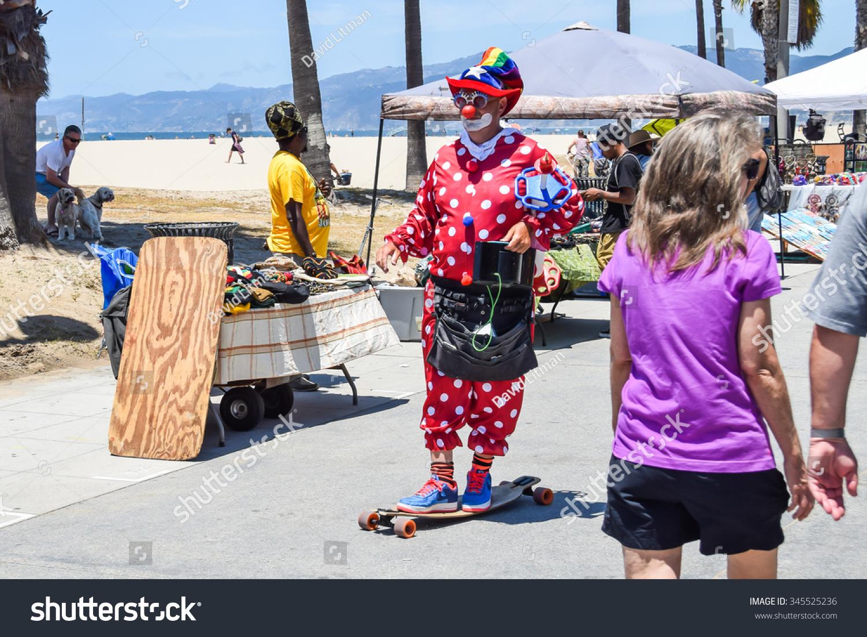 Venice, California, USA - July 12, 2015: A street clown rides a skateboard on the Venice Beach Boardwalk.