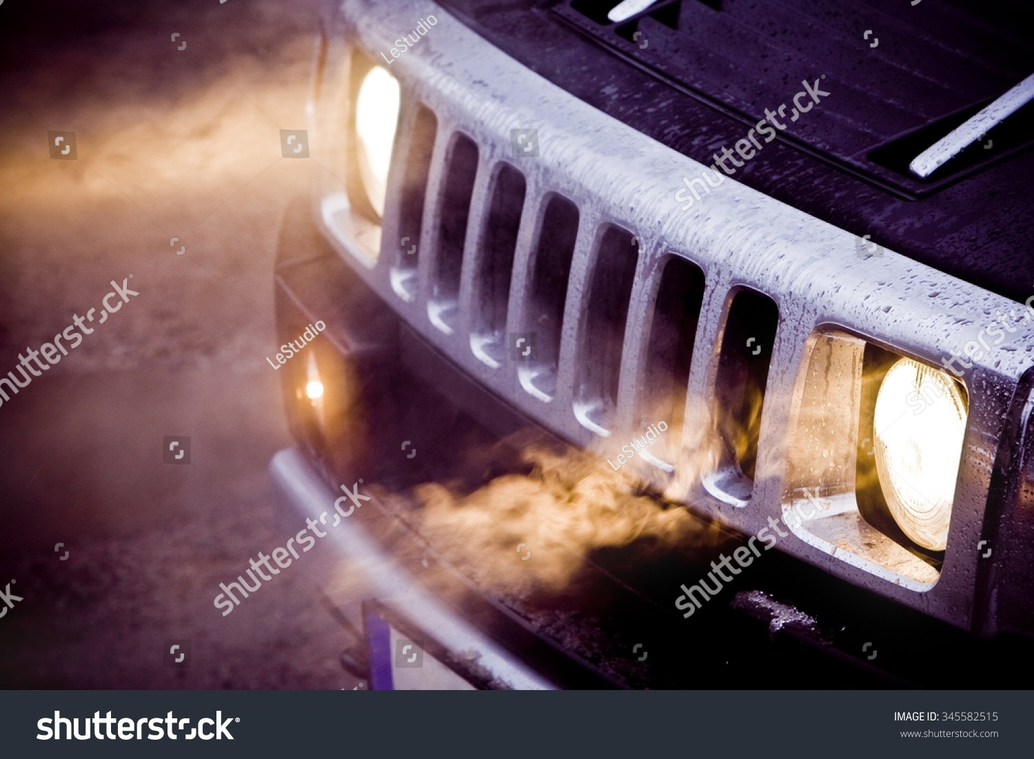 Headlights and chrome grille of a big powerful American SUV Hummer H2. Fog in the headlights of a black expensive off road car. Bad fuel milage or economy #345582515