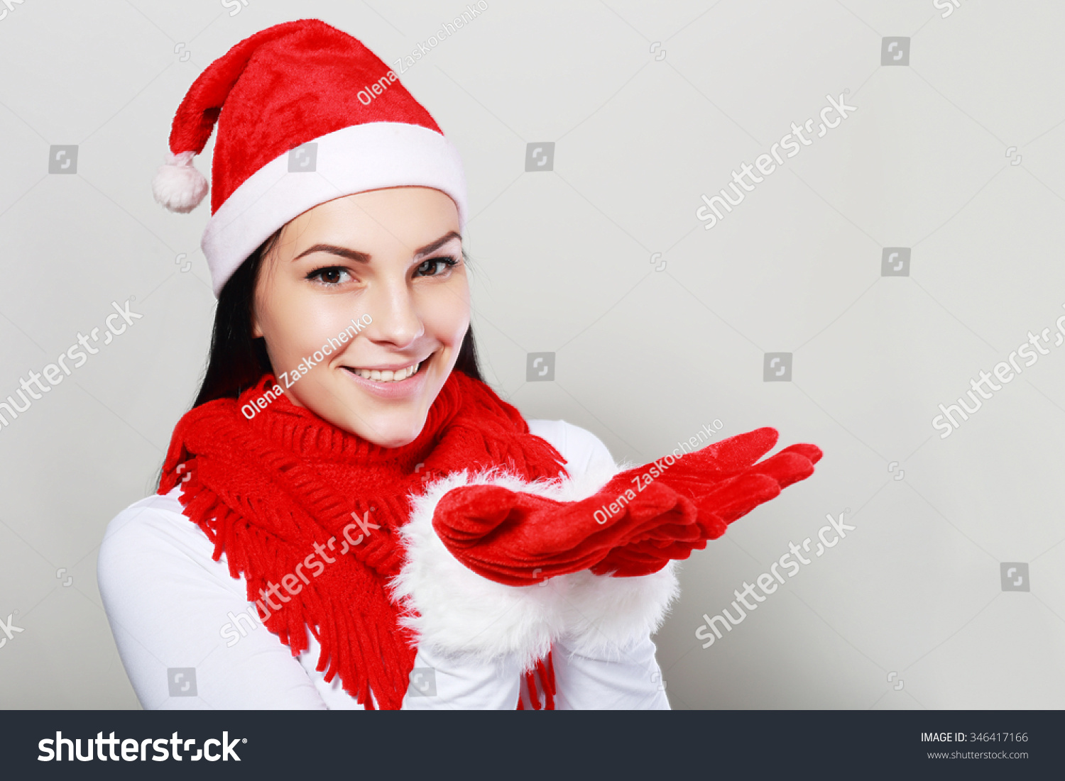 51d7bdea7d647 young christmas woman wearing a santa hat and smiling. Pesenting something  in her hands