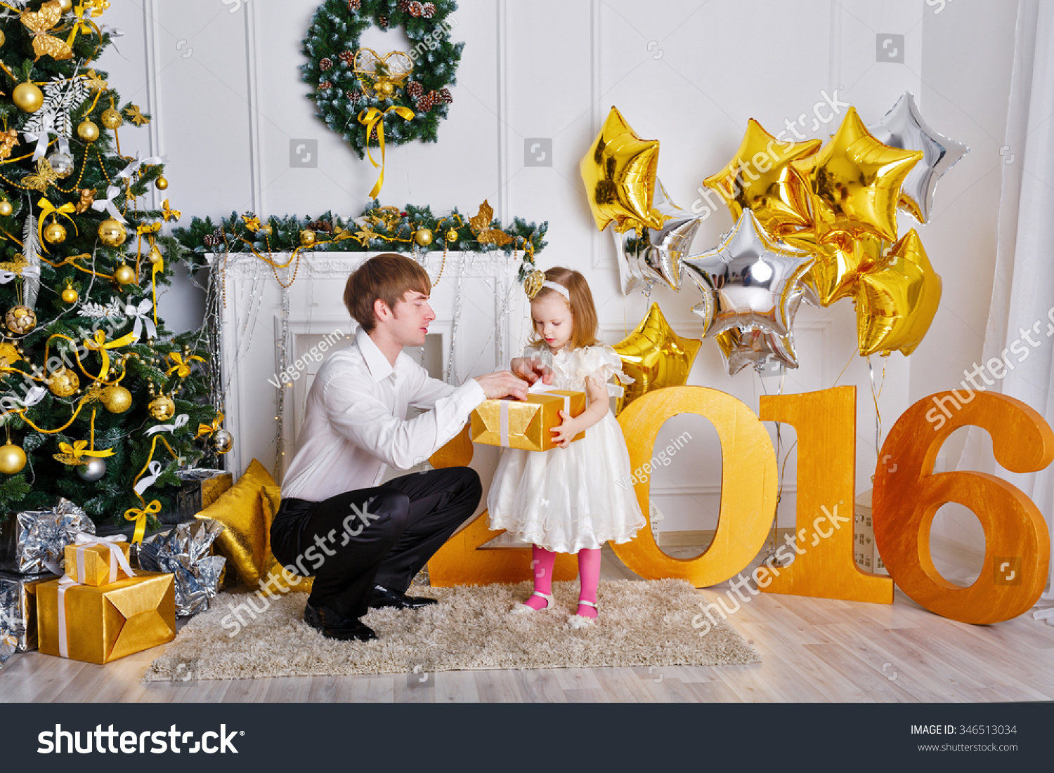 Father gives his daughter a gift for the New Year 2016 The concept of celebration and fun Family happiness Childhood