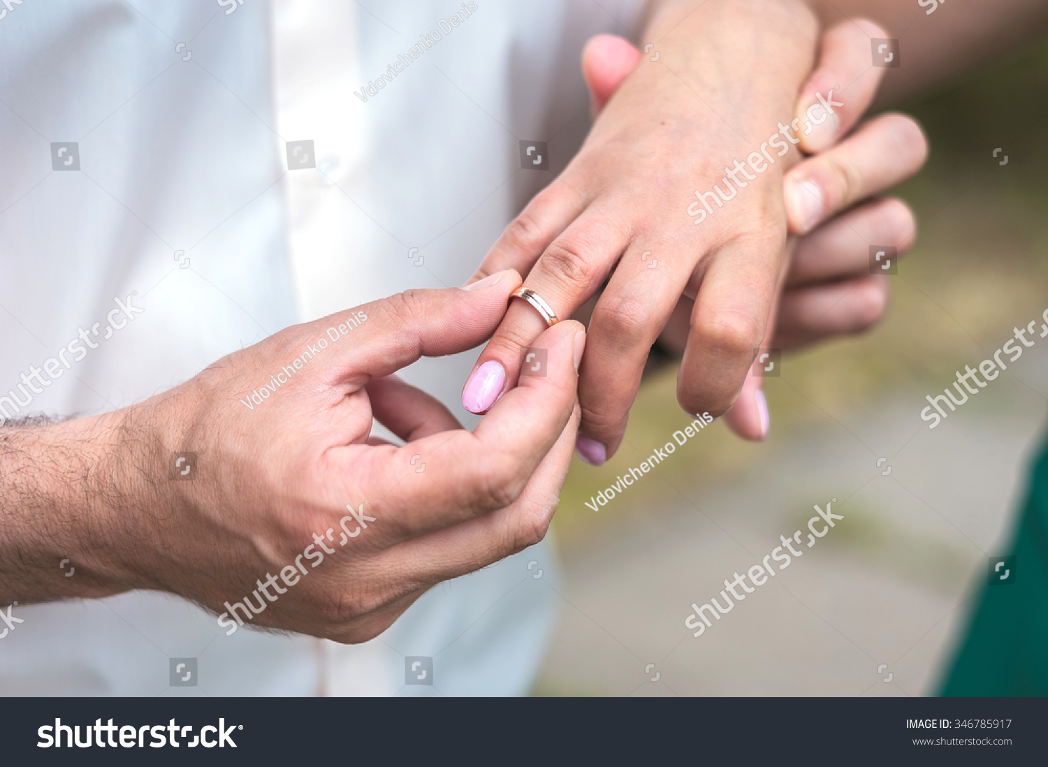 closeup of a groom putting a wedding ring onto the bride\'s finger ...