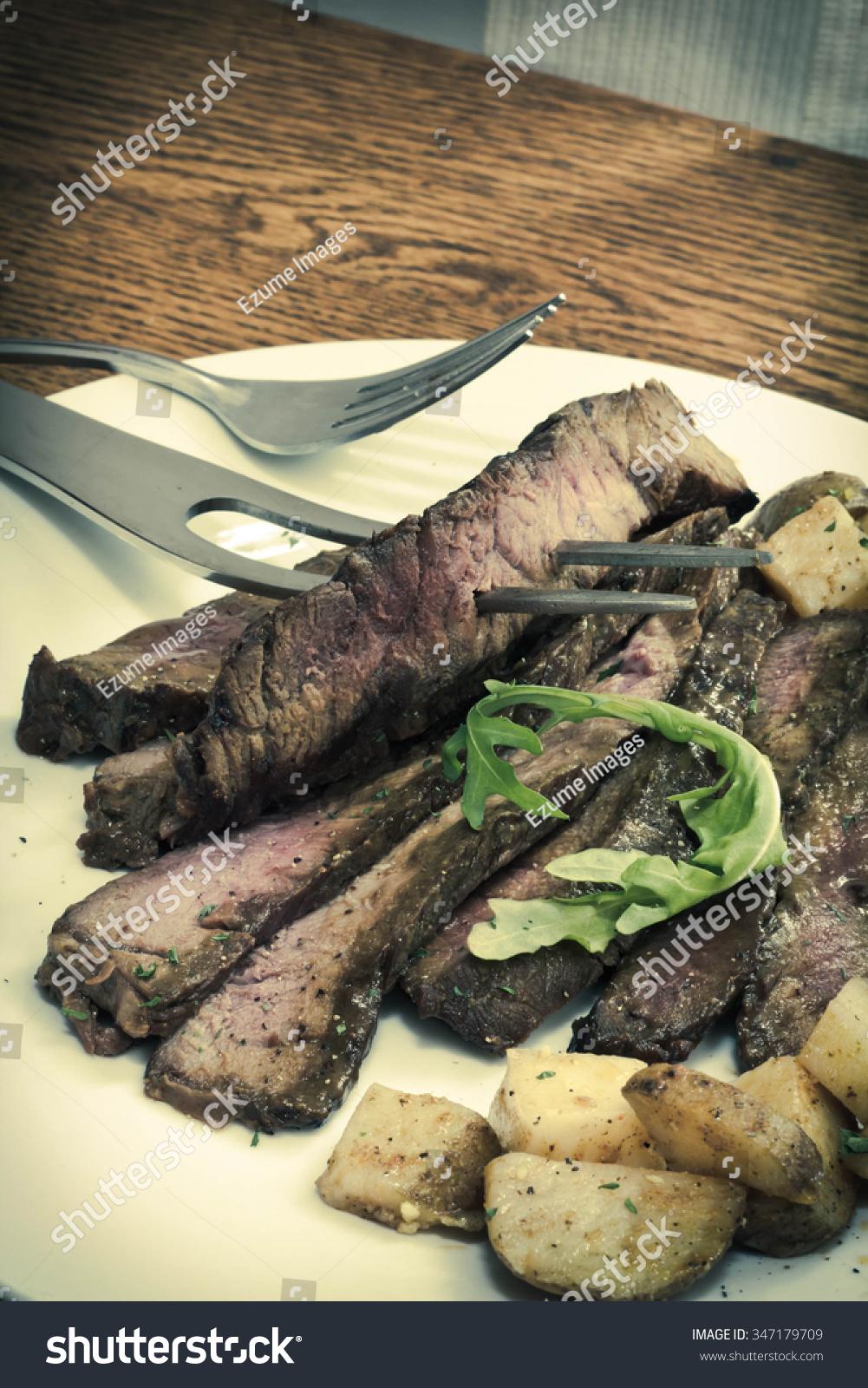Sliced Juicy Skirt Steak With Potatoes And Arugula Garnish Stock Photo ...