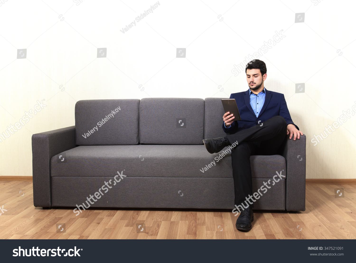 man with tablet pc sitting on the sofa stock photo 347521091 shutterstock. Black Bedroom Furniture Sets. Home Design Ideas