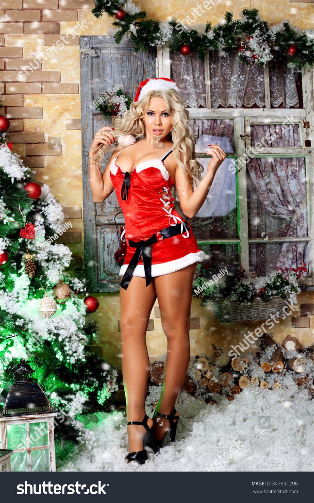 Beautiful sexy blonde female lush breasts model snowflake dressed Santa  Claus erotic red lingerie white fur