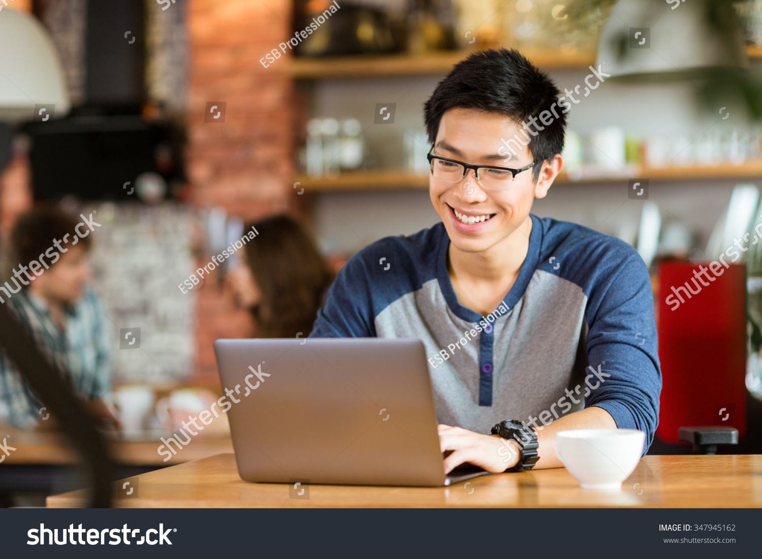 Happy cheerful young asian male in glasses smiling and using laptop in cafe #347945162