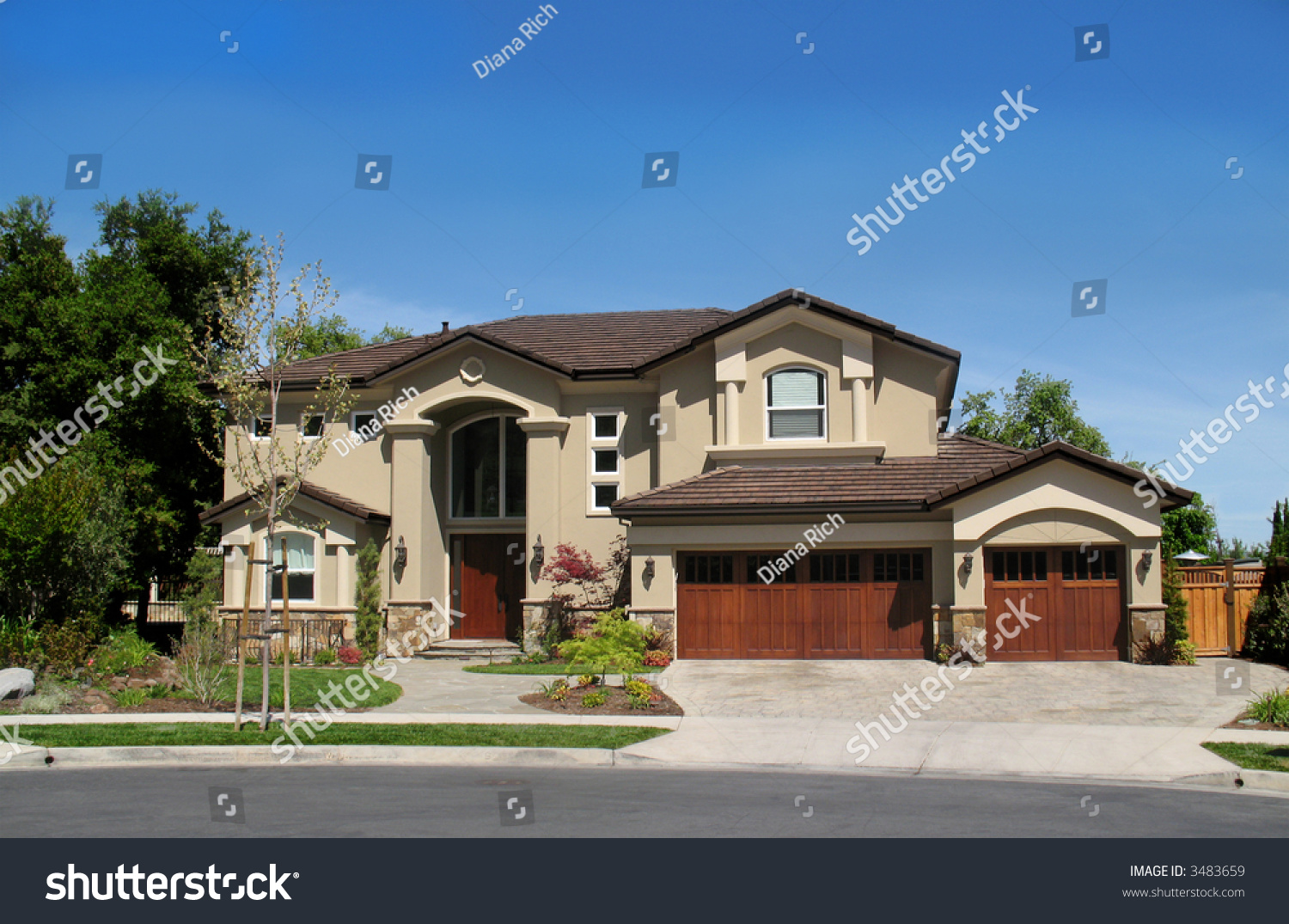 Large New Home With 3 Car Garage Against Blue Sky Stock