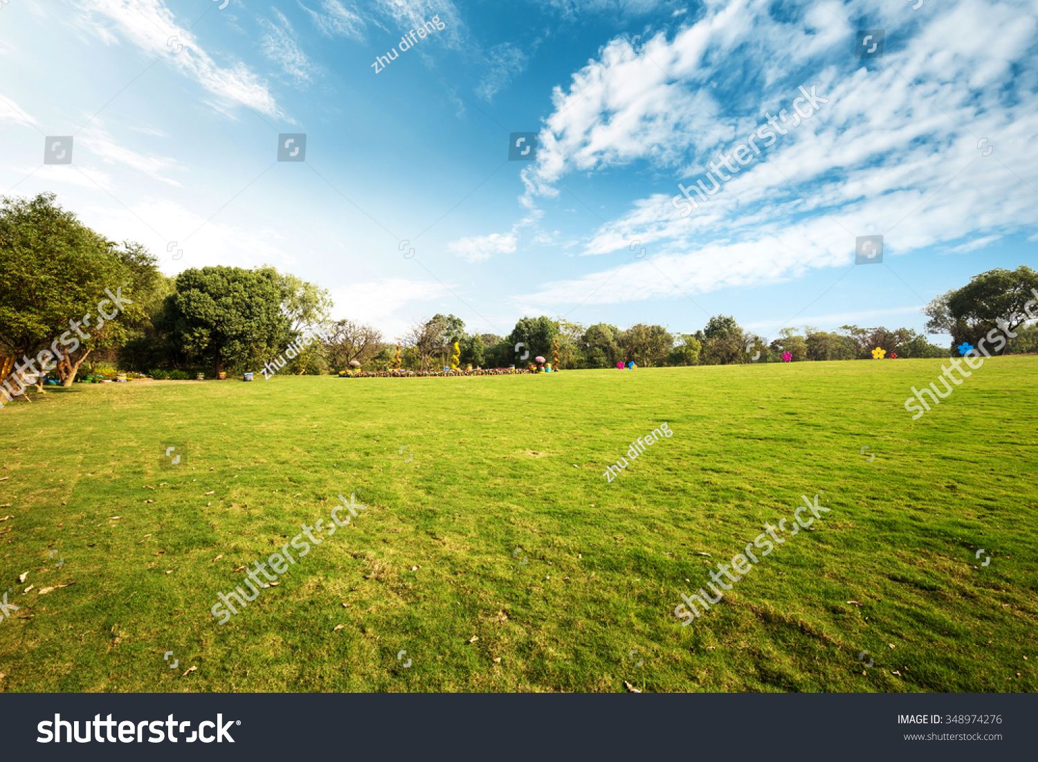 big meadow of city park in cloudy sky #348974276