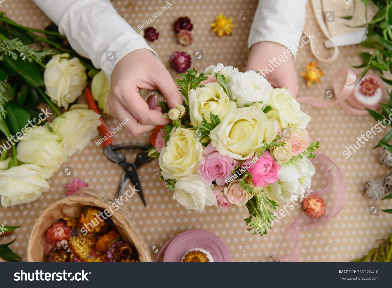 Florist hands making flower bouquet roses stock photo edit now florist hands making flower bouquet from roses view on the table from above izmirmasajfo