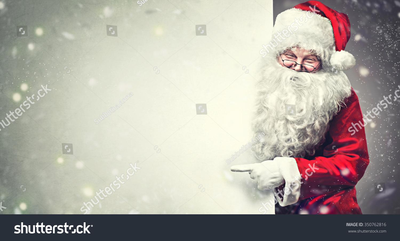 Happy santa claus pointing on blank stock photo