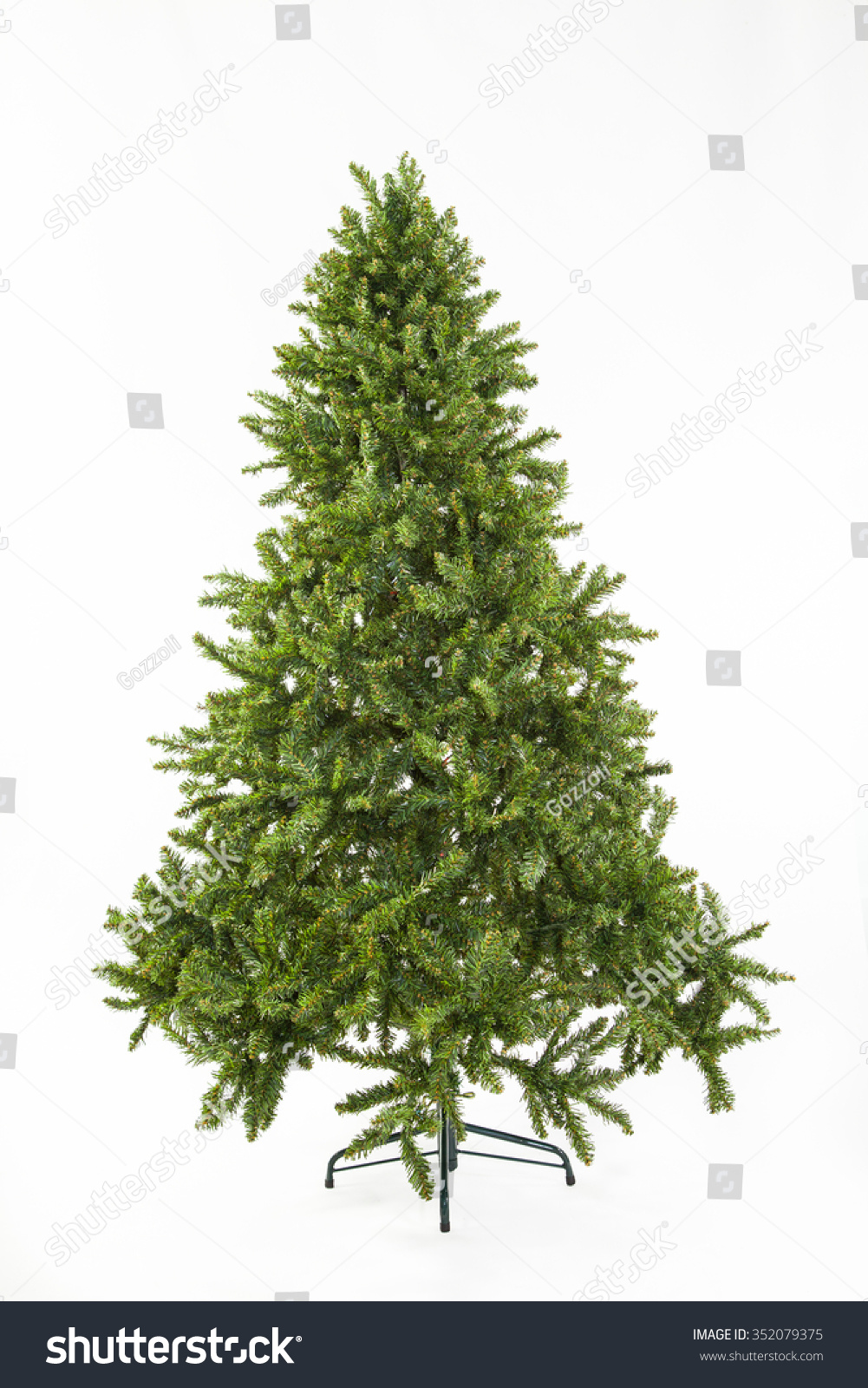 Undecorated bare green artificial Christmas tree on a metal stand over a white background for the festive holiday season #352079375