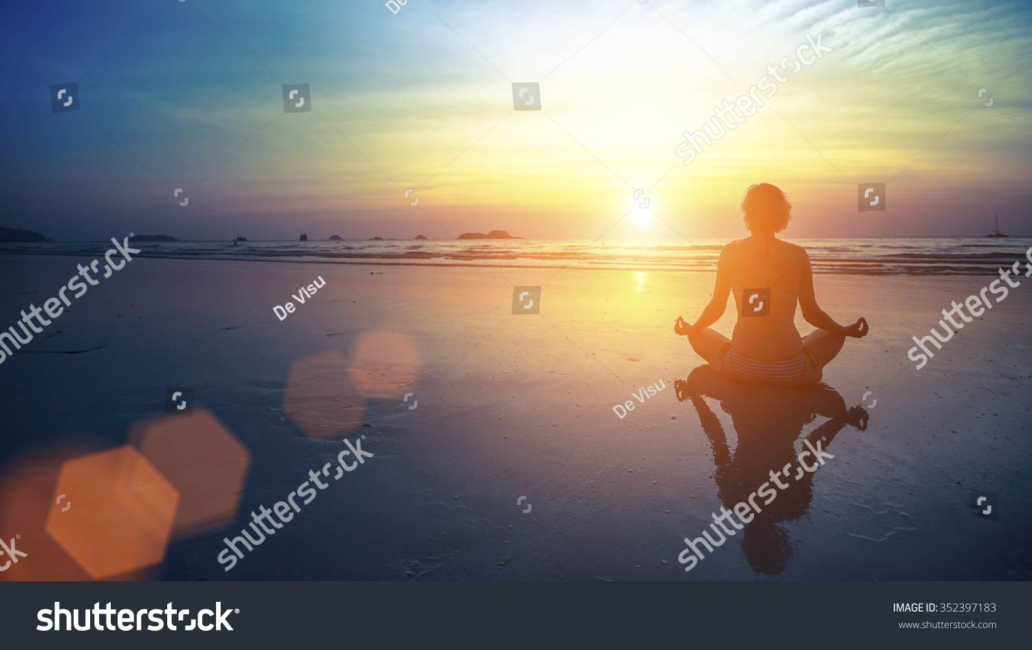 Young woman silhouette practicing yoga on the beach at amazing sunset